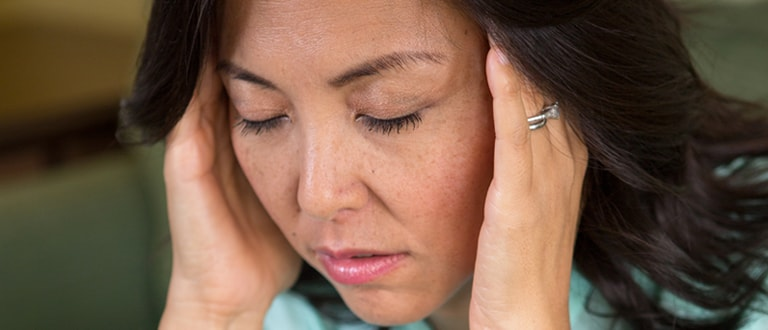 Image of woman having a headache with hands on her temples