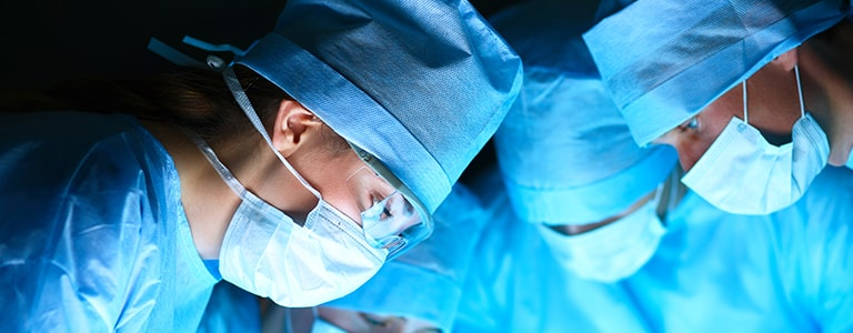 Image of 3 surgeons performing an operation